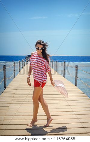 Young Woman Full Of Energy On A Pontoon In Front Of The Sea On A Sunny Day