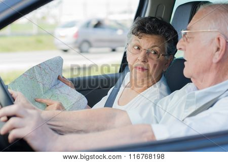 Elderly couple driving, wife pointing to map