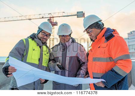 Young Civil Engineers And Senior Foreman At Construction Site