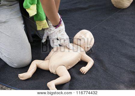 Infant dummy cardiac massage. First aid training.