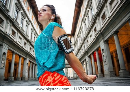 Now it is time to invest in your body and no matter you are at hometown or traveling. Female in sports outfit is stretching to start outdoors workout next to Uffizi gallery in Florence Italy poster