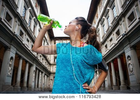 Now it is time to invest in your body and no matter you are at hometown or traveling. Sporty woman with headset is drinking water from the bottle in front of Uffizi gallery in Florence Italy poster