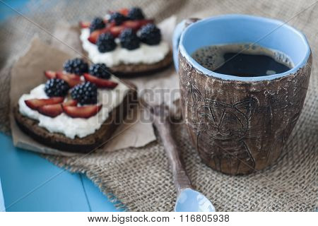 Sandwiches With Sweet Cheese And Berries, A Cup Of Coffee In Blue Wooden Background