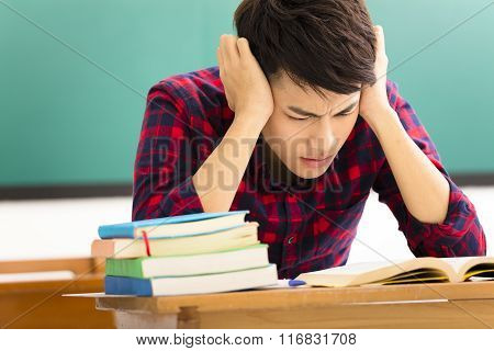 Stressed Student  Studying For Exam In Classroom