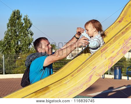 Father and baby child little boy playing on slide