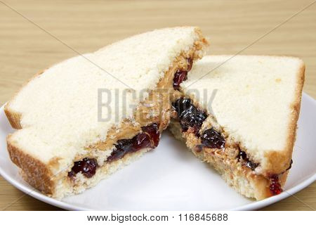 Peanutbutter And Jelly Sandwich Cut In Half Served On Plate On Wood Table
