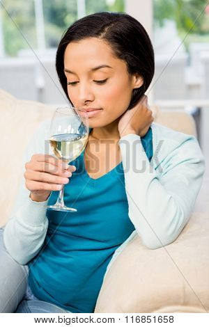 Peaceful brunette up to drink white whine while sitting on the sofa