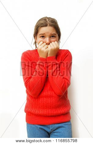 Portrait young little girl biting her finger nails, looking at you with fear of something, anxious isolated