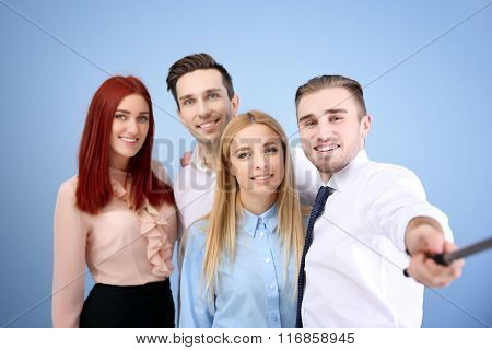 Young people using stick for group photo on blue wall background