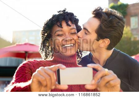 Happy couple having fun outdoor and taking selfie with smart phone. Young african woman smiling while the man kissing her on the cheek and taking a photo. Man kissing his girlfriend on the cheek.