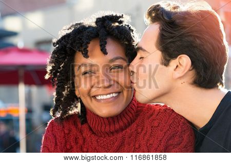 Young african woman is smiling while her boyfriend kissing her on the cheek. Close up face of young man kissing in woman's cheek while sitting at sidewalk cafe. Loving multi ethnic couple outdoor.