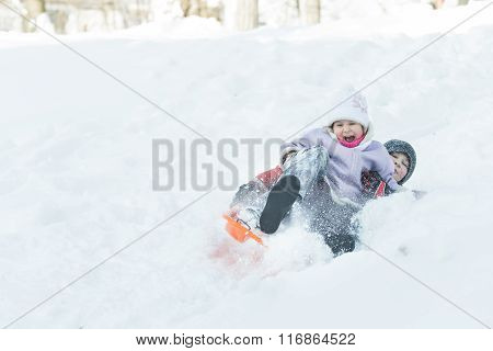 Two children sliding down snowy hill outdoors on orange plastic modern toboggan for kids