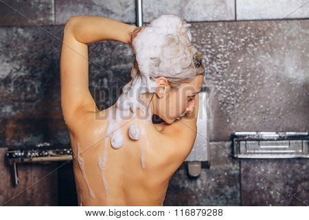 Beautiful woman standing at the shower. is washing her hair.