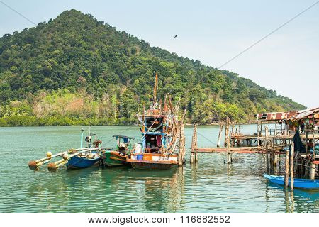 KOH CHANG, THAILAND - FEB 4, 2016: Huts and fishing boat at the pier in at fisherman village. In Thailand second most important occupation is fishing more 3% of population.
