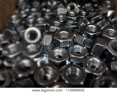 Metal ware background. Hex nuts in wooden box closeup
