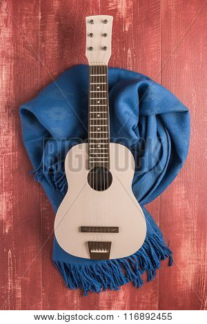 Guitar And Blanket On Rustic Wooden Background Texture