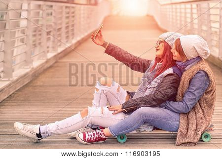 Hipster Girlfriends Taking A Selfie In Urban City Context Seat On Skate