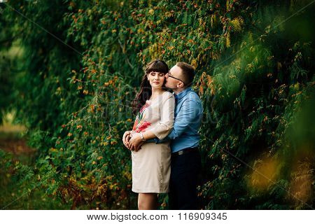 Pregnant Woman And Her Handsome Husband Lovely Hugging  On Nature, Have Picnic In Park.