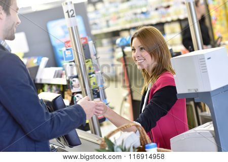 Portrait of cashier with customer paying grocery products