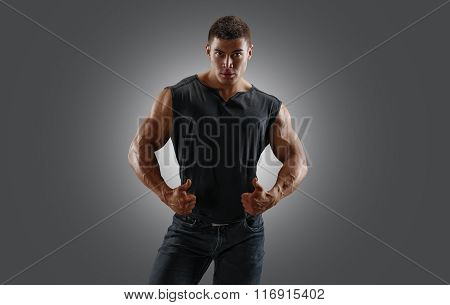 Strong muscular man in a T-shirt and jeans, showing raised up thumbs. Gray background