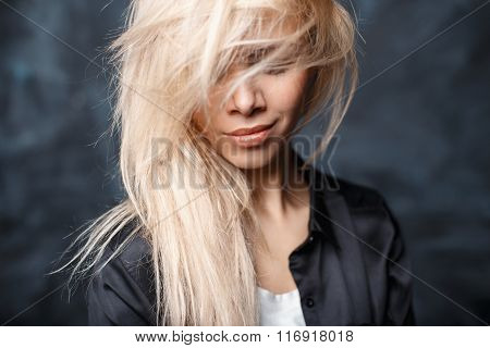 Close-up Portrait Of A Beautiful Woman With Tousled Blond Hair And Beautiful Lips In A Stylish Black