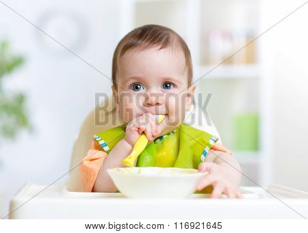 kid baby eating food on kitchen