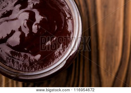Homemade DIY natural  nutella - chocolate jam made of plums, cacao powder and vanilla. Healthy marmalade in glass jar on a wooden table poster