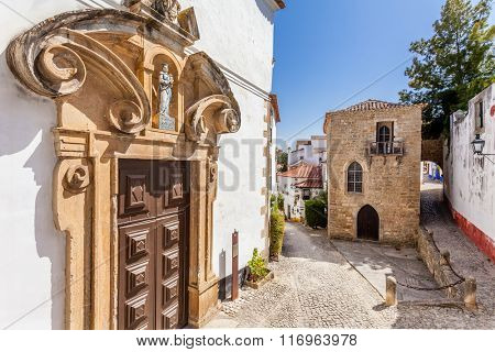 Obidos, Portugal - August, 2015: Misericordia Church portal and the Medieval Sephardic Synagogue in background. Obidos is a medieval town inside walls, and very popular among tourists.