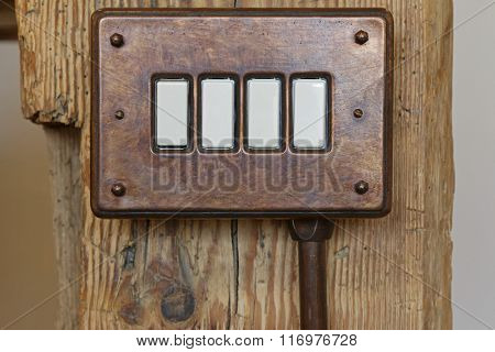 Closeup of vintage bakelite toggle light switch in brown on wooden pole