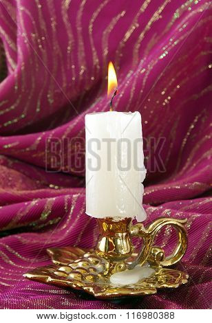 candle burning in a candlestick