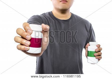 Male comparing bottles of medicine or dietary supplements poster