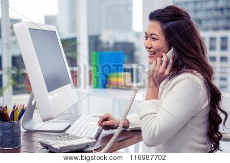 Smiling Asian woman on phone call using computer in office