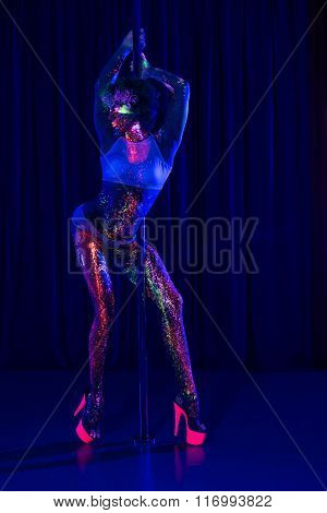 woman dancing striptease with neon body art in ultraviolet light
