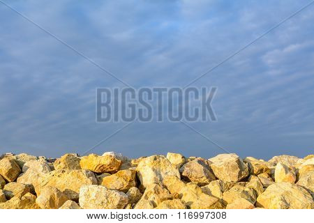 Rocks Over Blue Clear Sky. Backgroung With Clear Blue Sky Meeting Multitude Of Yellow Rocks On Dayti