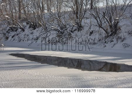 Osha river in Siberia high snowy banks unfrozen patch of water sunny day wood