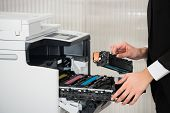 Midsection of young businessman fixing cartridge in printer machine at office poster