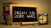 Dream Big Work Hard Handwritten on Chalkboard. Motivational Quote. Composition with Chalkboard and Stack of Books, Alarm Clock and Scrolls on Blurred Background. Toned Image. poster
