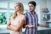 Upset couple having an argument in the kitchen poster