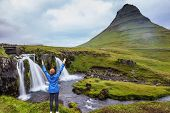 Middle-aged woman tourist admires the beauty of nature. Threaded full-flowing waterfall Kirkjufell Foss on the grassy mountains poster