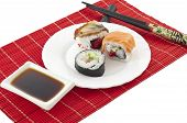The Sushi the chopsticks soya sauce on a red bamboo mat on a white background poster