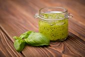 Natural homemade DIY vegan very healthy green pesto made of radish leaves and nutritional yeast flakes in a glass jar on a wooden table poster