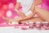Midsection of beautician waxing woman's leg with wax strip at salon poster