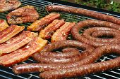 grilled pork meat lamb chops and sausages on a grill for a barbecue (south african braai) outdoors in south africa poster
