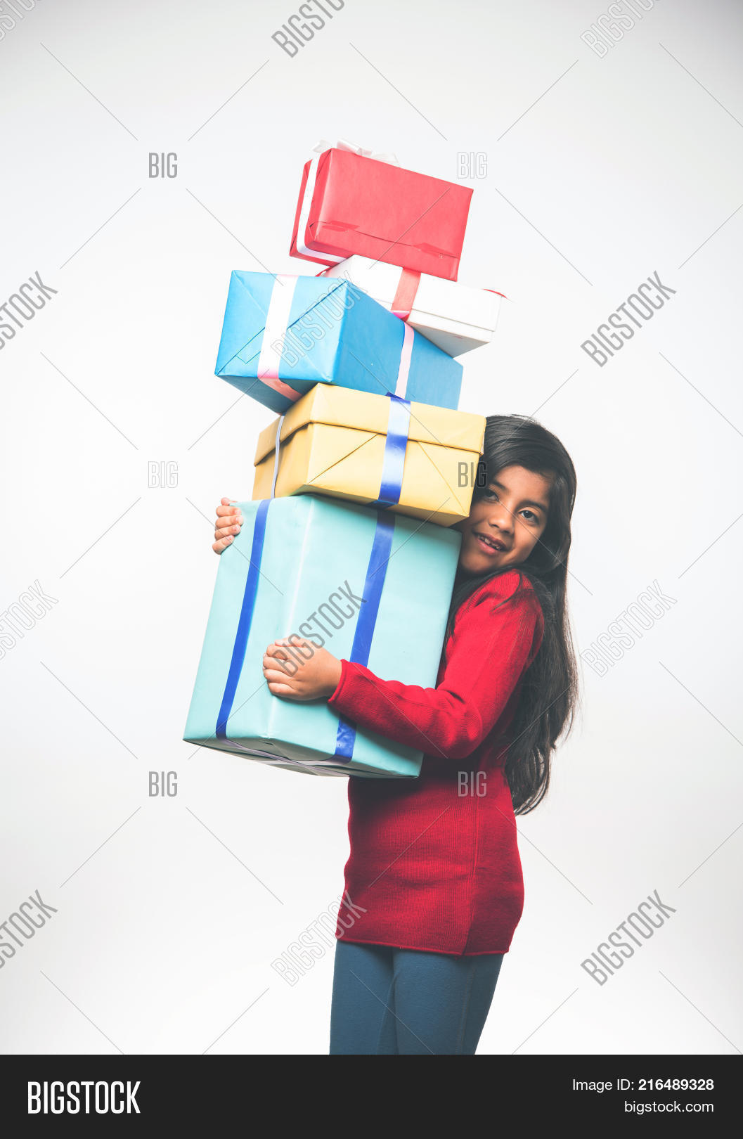 ec5968d7cdc5 Little Indian girl holding christmas gifts in red cloths or santa clause  hat and attire,