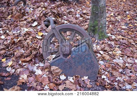 Rusty old mine pulley laying in leaves on ground