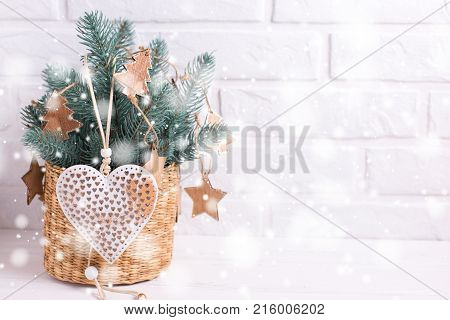 Christmas toys heart and branches fur tree on white wooden background. Decorative christmas composition. Selective focus. Place for text. Drawn snow effect.