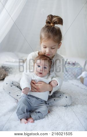 Little Girl Embracing A  Newborn Baby Brother. Little Girl And Baby Boy Brother And Sister Playing I