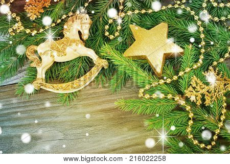 Christmas background with a toy horse gold star green fir branches and other decorations on old wooden planks