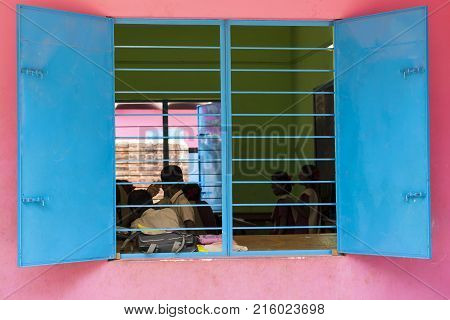 PONDICHERY PUDUCHERY INDIA - SEPTEMBER 04 2017. Pink and blue school with chidren looking out the window