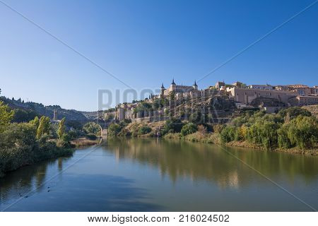 Scenery of Toledo city in Spain Europe. Green water river Tagus Alcantara arch bridge landmark and monument from ancient Roman age and alcazar building